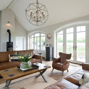 Esempio di un grande soggiorno rustico aperto con pareti grigie, parquet chiaro, stufa a legna e pavimento beige