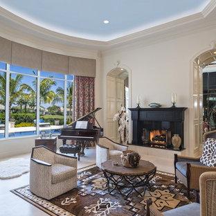 Modelo de salón con rincón musical mediterráneo, sin televisor, con paredes beige, chimenea tradicional y suelo beige