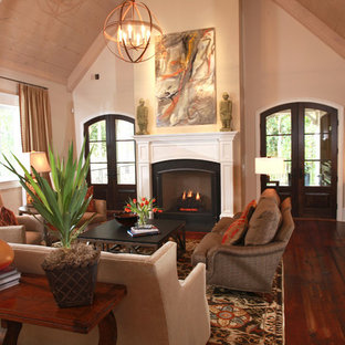 Example of a mid-sized classic formal and enclosed medium tone wood floor living room design in Atlanta with beige walls, a standard fireplace, a concrete fireplace and no tv