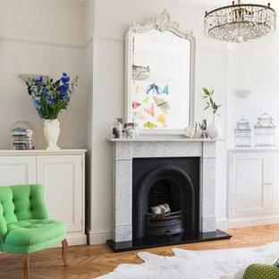 マンチェスターの北欧スタイルのおしゃれなリビング (ベージュの壁、無垢フローリング、標準型暖炉、石材の暖炉まわり、オレンジの床) の写真