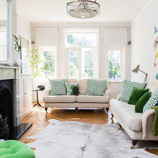 Design ideas for a medium sized scandi enclosed living room in Manchester with white walls, medium hardwood flooring, a standard fireplace, a stone fireplace surround and brown floors.