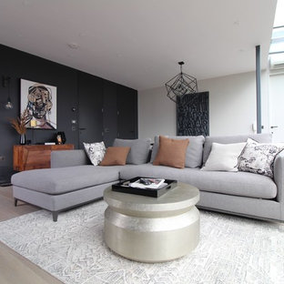 This is an example of a medium sized modern enclosed living room in London with white walls and light hardwood flooring.