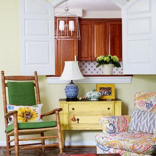 Immagine di un soggiorno country chiuso con nessuna TV, pareti gialle, pavimento in mattoni e pavimento marrone