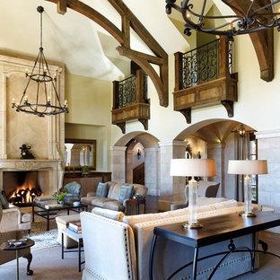 Exemple d'un très grand salon fermé avec une cheminée standard, une salle de réception, un mur beige, un sol en bois foncé, un manteau de cheminée en pierre et aucun téléviseur.