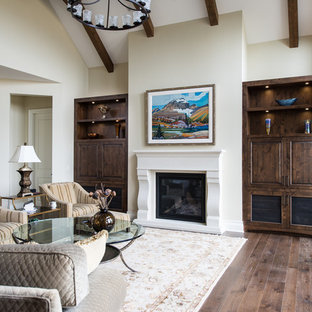 Inspiration for a large traditional open concept living room in Vancouver with beige walls, medium hardwood floors, a standard fireplace, a concrete fireplace surround and a concealed tv.