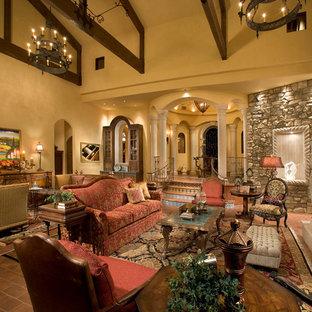 Esempio di un ampio soggiorno mediterraneo aperto con sala formale, pareti beige, pavimento in mattoni, camino classico, cornice del camino in pietra e pavimento rosso