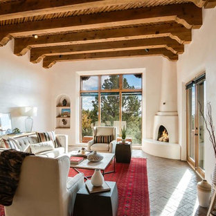 Example of a large southwest formal and open concept brick floor and brown floor living room design in Other with white walls, a corner fireplace, a plaster fireplace and no tv