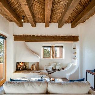 他の地域の小さいサンタフェスタイルのおしゃれな独立型リビング (白い壁、レンガの床、コーナー設置型暖炉、漆喰の暖炉まわり、テレビなし、茶色い床) の写真