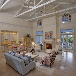 Ispirazione per un soggiorno tropicale con angolo bar, pavimento in marmo, pareti bianche e camino classico