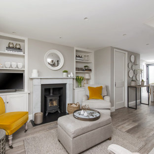 Design ideas for a large classic open plan living room in London with grey walls, a wood burning stove, a metal fireplace surround, a freestanding tv and grey floors.