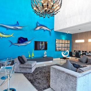 Idee per un soggiorno tropicale aperto con pareti blu e TV a parete