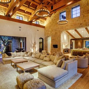 Ejemplo de salón abierto, mediterráneo, con paredes beige y suelo de madera en tonos medios