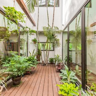 Esempio di un soggiorno di medie dimensioni e aperto con pareti bianche, pavimento in terracotta, camino classico, cornice del camino in legno, TV a parete e pavimento marrone