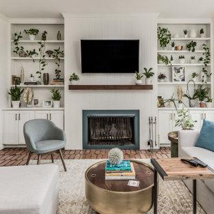 Ispirazione per un soggiorno di medie dimensioni e aperto con pareti bianche, pavimento in terracotta, camino classico, cornice del camino in legno, TV a parete e pavimento marrone