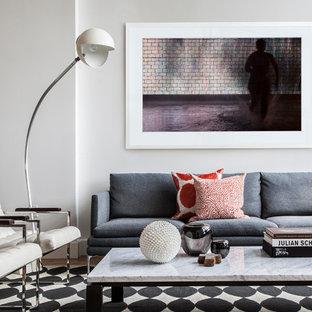 Diseño de salón para visitas cerrado, actual, de tamaño medio, sin chimenea, con paredes blancas, suelo de madera clara, pared multimedia y suelo marrón