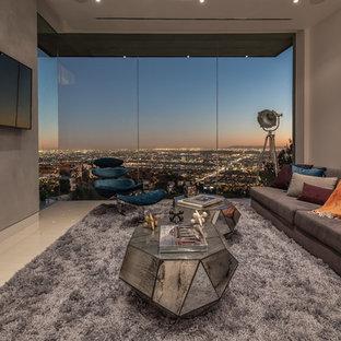 Modern inredning av ett separat vardagsrum, med grå väggar och en väggmonterad TV