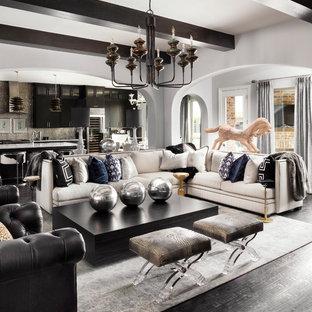Imagen de salón abierto, tradicional renovado, con paredes grises y suelo de madera oscura