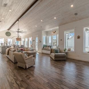 ヒューストンの広いビーチスタイルのおしゃれなLDK (ベージュの壁、セラミックタイルの床、暖炉なし、茶色い床) の写真