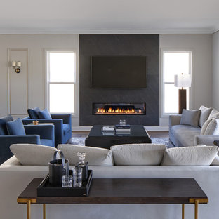 Inspiration for a medium sized contemporary open plan living room in Los Angeles with black walls, medium hardwood flooring, a ribbon fireplace, a stone fireplace surround, a wall mounted tv, brown floors and feature lighting.