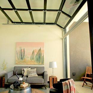 Foto di un piccolo soggiorno moderno aperto con libreria, pareti beige, pavimento in pietra calcarea, nessun camino, nessuna TV e pavimento grigio