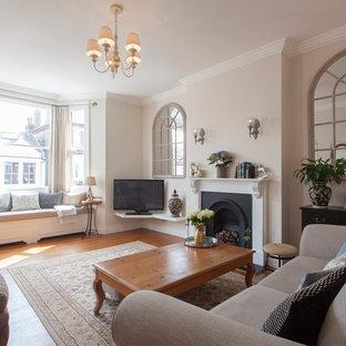 ロンドンの中サイズのトラディショナルスタイルのおしゃれなLDK (ベージュの壁、無垢フローリング、標準型暖炉、木材の暖炉まわり、据え置き型テレビ) の写真