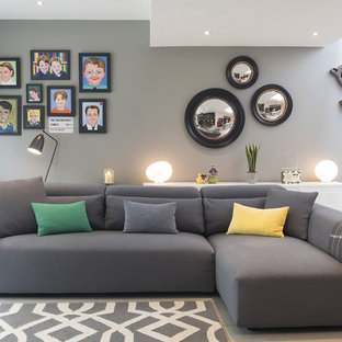 This is an example of a contemporary open plan living room in London with grey walls.