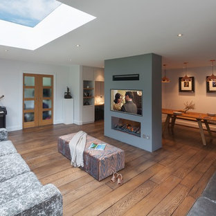 Design ideas for a large contemporary open concept living room in Surrey with a home bar, grey walls, medium hardwood floors, a two-sided fireplace, a plaster fireplace surround, a wall-mounted tv and brown floor.