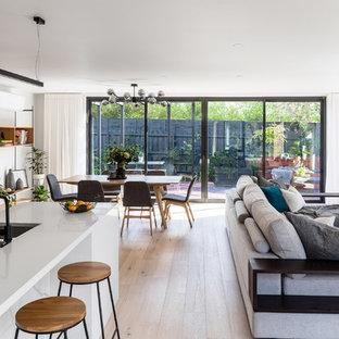 Idee per un soggiorno minimalista di medie dimensioni e aperto con pareti bianche, pavimento in laminato, parete attrezzata e pavimento marrone