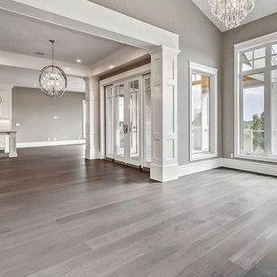 サリーの巨大なトラディショナルスタイルのおしゃれなLDK (フォーマル、白い壁、塗装フローリング、両方向型暖炉、石材の暖炉まわり、埋込式メディアウォール、茶色い床、塗装板張りの天井、壁紙) の写真