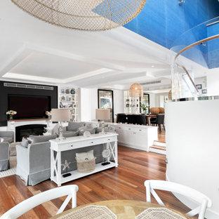 Ejemplo de salón abierto y boiserie, costero, grande, boiserie, con paredes blancas, suelo de madera en tonos medios, chimenea tradicional, marco de chimenea de piedra, pared multimedia y boiserie