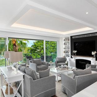 シドニーの広いビーチスタイルのおしゃれなLDK (白い壁、無垢フローリング、標準型暖炉、石材の暖炉まわり、埋込式メディアウォール、折り上げ天井、羽目板の壁) の写真