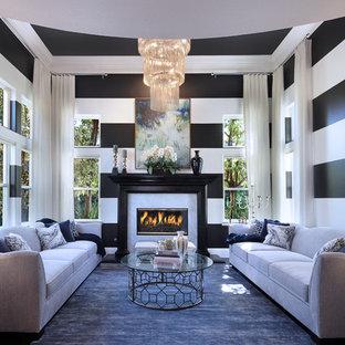 Foto di un soggiorno chic di medie dimensioni e aperto con sala formale, pareti nere, parquet scuro, camino classico, cornice del camino piastrellata, nessuna TV e pavimento marrone