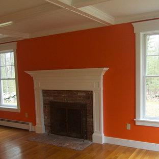 Modelo de salón para visitas cerrado, clásico, pequeño, sin televisor, con parades naranjas, suelo de madera clara, chimenea tradicional, marco de chimenea de ladrillo y suelo beige
