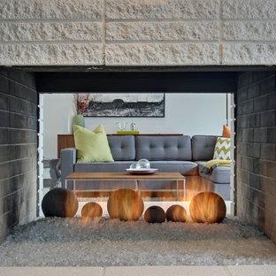 Ispirazione per un soggiorno minimal di medie dimensioni e aperto con pareti bianche, pavimento in cemento, camino bifacciale, cornice del camino in mattoni e TV a parete