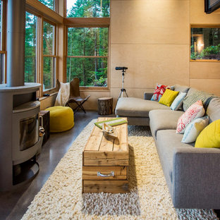 Photo of a medium sized rustic formal living room in Seattle with concrete flooring, a wood burning stove, beige walls, a metal fireplace surround and no tv.