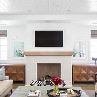 オレンジカウンティの大きいトロピカルスタイルのおしゃれなLDK (白い壁、無垢フローリング、標準型暖炉、タイルの暖炉まわり、壁掛け型テレビ、茶色い床) の写真