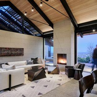 オースティンの中くらいのコンテンポラリースタイルのおしゃれなLDK (ベージュの壁、コンクリートの床、標準型暖炉、石材の暖炉まわり、グレーの床、板張り天井) の写真