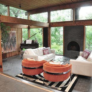 Foto de salón abierto, moderno, extra grande, con suelo de ladrillo, chimenea tradicional y marco de chimenea de ladrillo