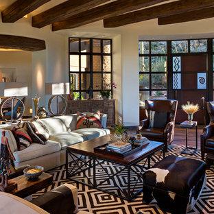 フェニックスの広いサンタフェスタイルのおしゃれなLDK (フォーマル、ベージュの壁、無垢フローリング、標準型暖炉、石材の暖炉まわり、埋込式メディアウォール、茶色い床) の写真