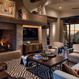 フェニックスの大きいサンタフェスタイルのおしゃれなLDK (ベージュの壁、標準型暖炉、フォーマル、無垢フローリング、石材の暖炉まわり、埋込式メディアウォール、茶色い床) の写真
