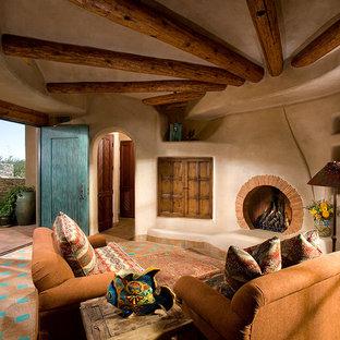 フェニックスのサンタフェスタイルのおしゃれなリビング (ベージュの壁、テラコッタタイルの床、標準型暖炉、漆喰の暖炉まわり) の写真