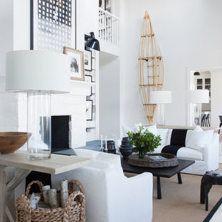 ニューヨークのビーチスタイルのおしゃれなリビング (白い壁、塗装フローリング、標準型暖炉、石材の暖炉まわり、白い床) の写真
