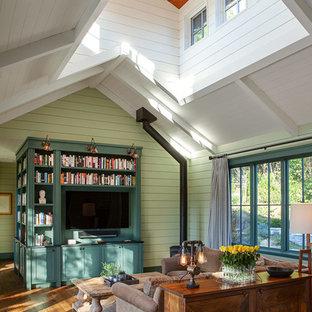 Réalisation d'un salon champêtre avec un mur vert, un sol en bois brun, un poêle à bois, un téléviseur fixé au mur et un sol marron.