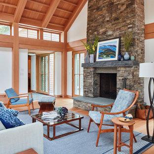 Idée de décoration pour un salon champêtre avec un mur blanc, un sol en bois brun, une cheminée standard, un manteau de cheminée en pierre et un sol marron.