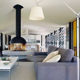 Trendy open concept dark wood floor living room photo in Melbourne with white walls and a wood stove