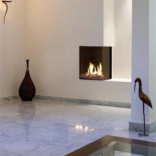 Esempio di un soggiorno minimalista con pareti bianche, pavimento in marmo, camino ad angolo e cornice del camino in intonaco