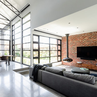 Inspiration for an industrial open concept living room in Melbourne with white walls, concrete floors, a hanging fireplace, a wall-mounted tv, grey floor and brick walls.
