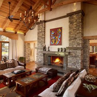 Réalisation d'un grand salon sud-ouest américain avec un mur beige, une cheminée standard et un manteau de cheminée en pierre.
