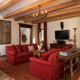 Diseño de salón cerrado, rústico, de tamaño medio, con suelo de ladrillo, paredes beige y televisor colgado en la pared