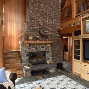 ミネアポリスのエクレクティックスタイルのおしゃれなリビング (標準型暖炉、石材の暖炉まわり、スレートの床) の写真